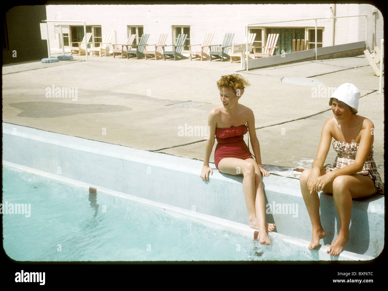 Two pretty women sit on edge of motel hotel swmimming pool fashion bathing suit swim suit 1959s 1950s fashionable - Stock Image