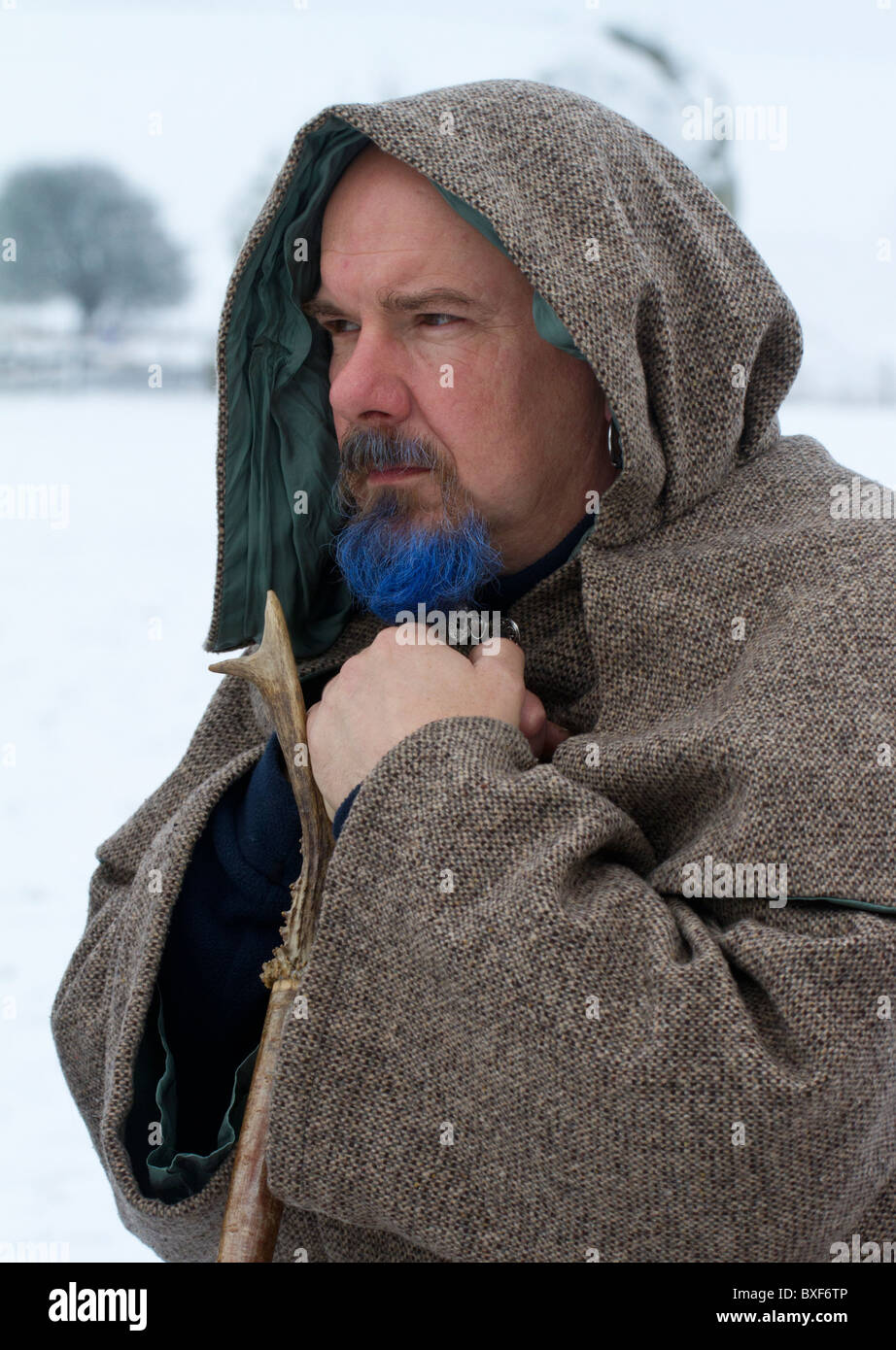 Druid celebrating the Winter Solstice in the snow at Avebury stone circle, Wiltshire, UK - Stock Image