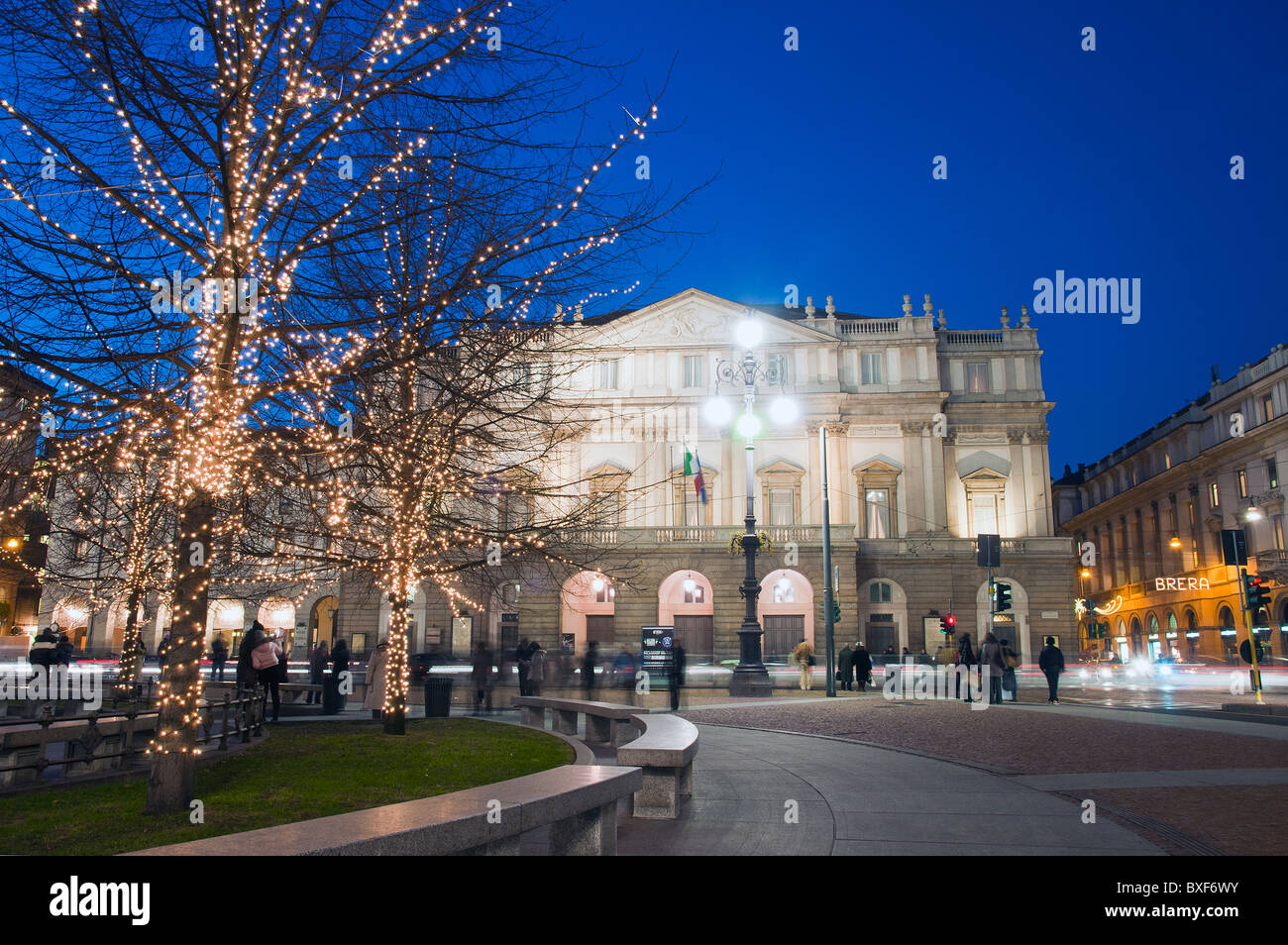 View of La Scala opera theatre at dusk behind the trees decorated with Christmas lights, Milan, Italy - Stock Image