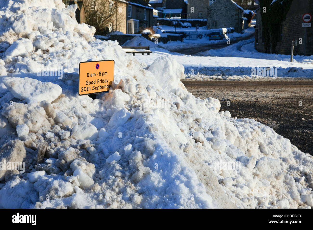 England, UK. Deep snow piled up by roadside restricted parking sign during severe winter weather causing traffic - Stock Image