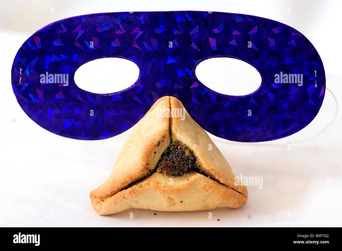 Studio Photo of blue mask and hamantash pastry traditionally eaten on the Jewish holiday of Purim isolated on white - Stock Image