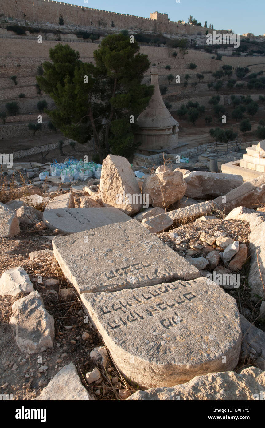Old gravestone with hebrew writings at mount of Olives with old city walls in bkgd. Jerusalem - Stock Image