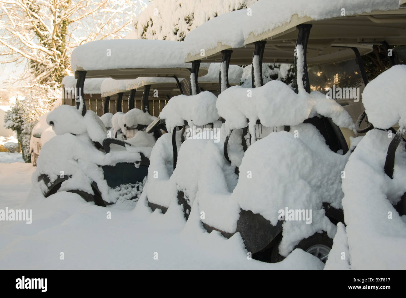 Golf buggies covered in snow at a rural Welsh golf club - Stock Image