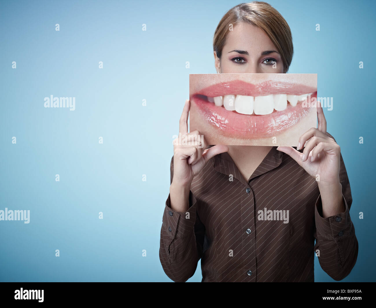 mid adult business woman holding photo of toothy smile on blue background. Horizontal shape, front view, waist up, - Stock Image