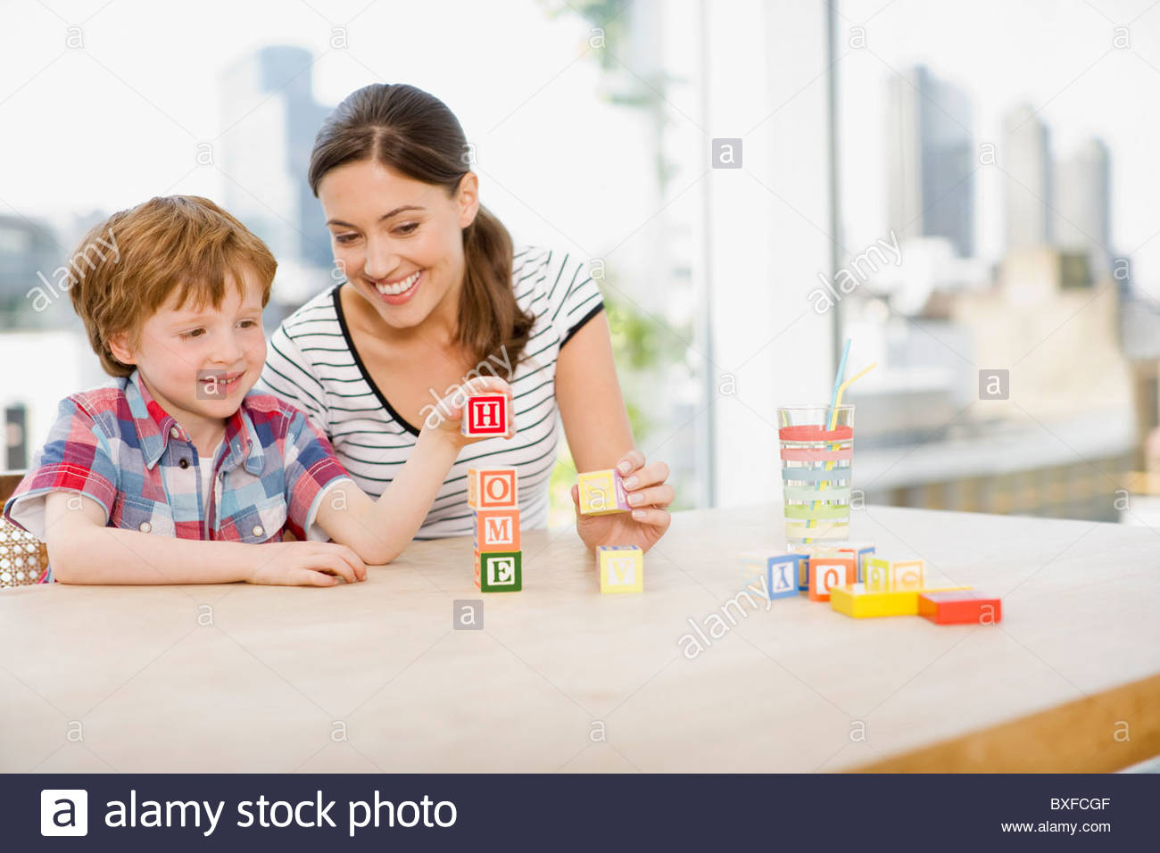 Mother watching son stacking alphabet blocks and spelling 'home' - Stock Image