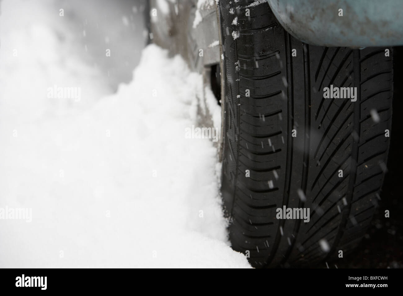 snow drifting up against a car tyre on a cold snowy winters day - Stock Image