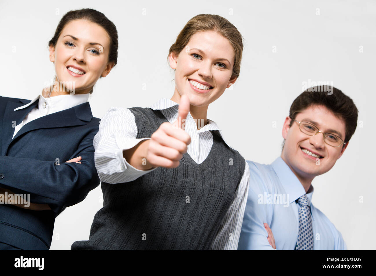 Smiling woman demonstrates thumb up with business people Stock Photo
