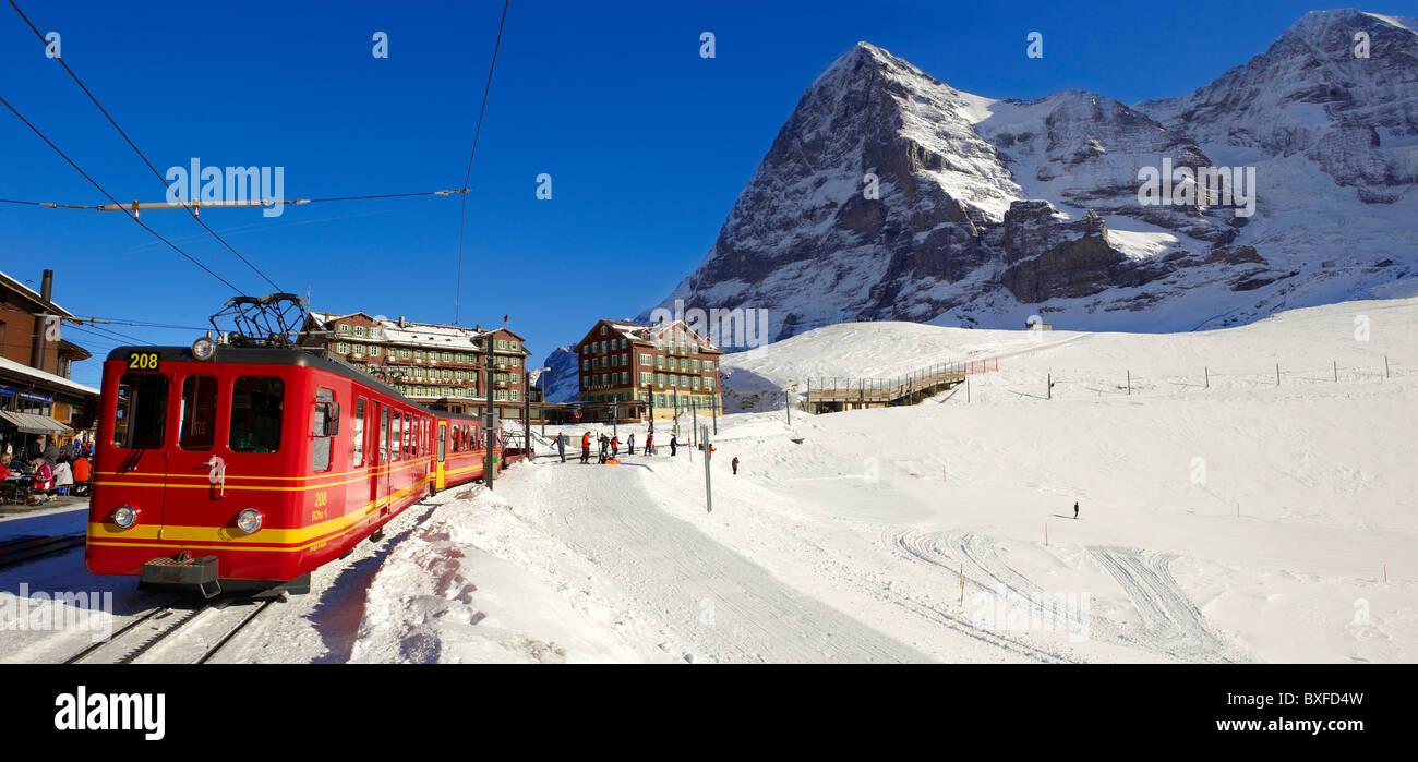 Jungfraujoch train at Kleiner Scheidegg in winter with The Eiger (left) then The Monch Mountains. Swiss Alps Switzerland - Stock Image