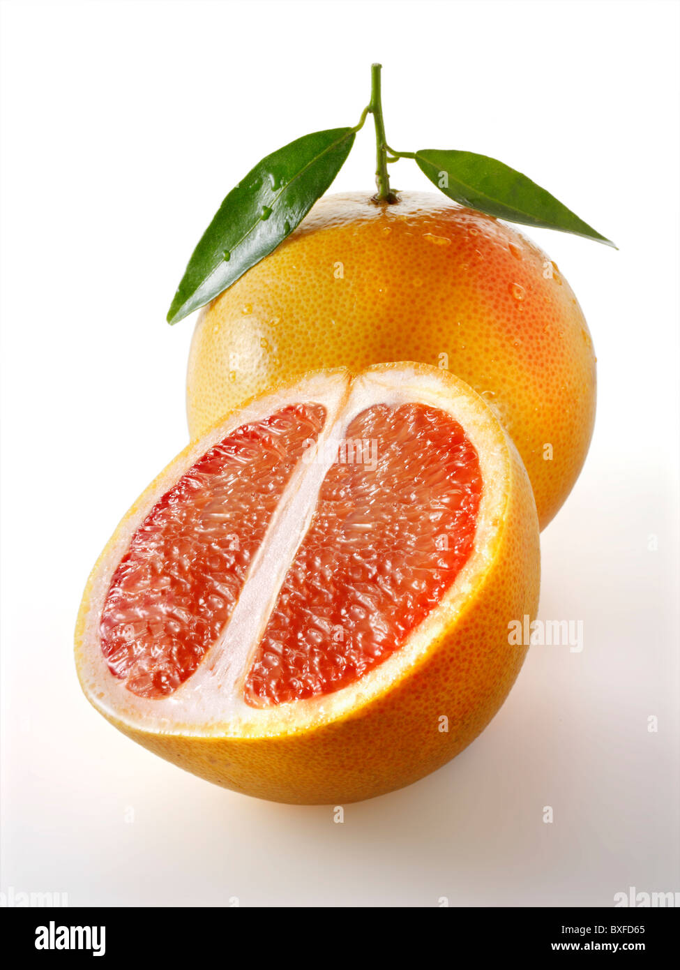 Fresh whole and cut pink grapefruit with leaves against a white background - Stock Image