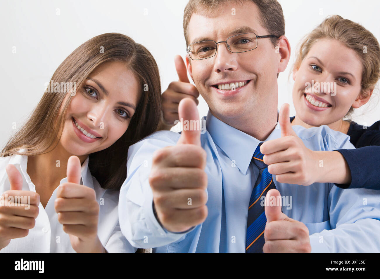 Team of three office worker's give the thumb's up sign Stock Photo