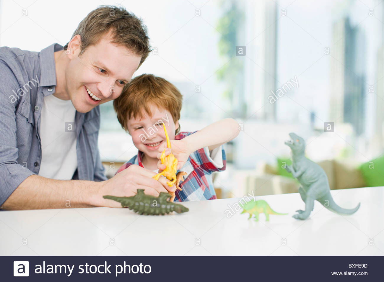 Father and son playing with plastic dinosaurs - Stock Image