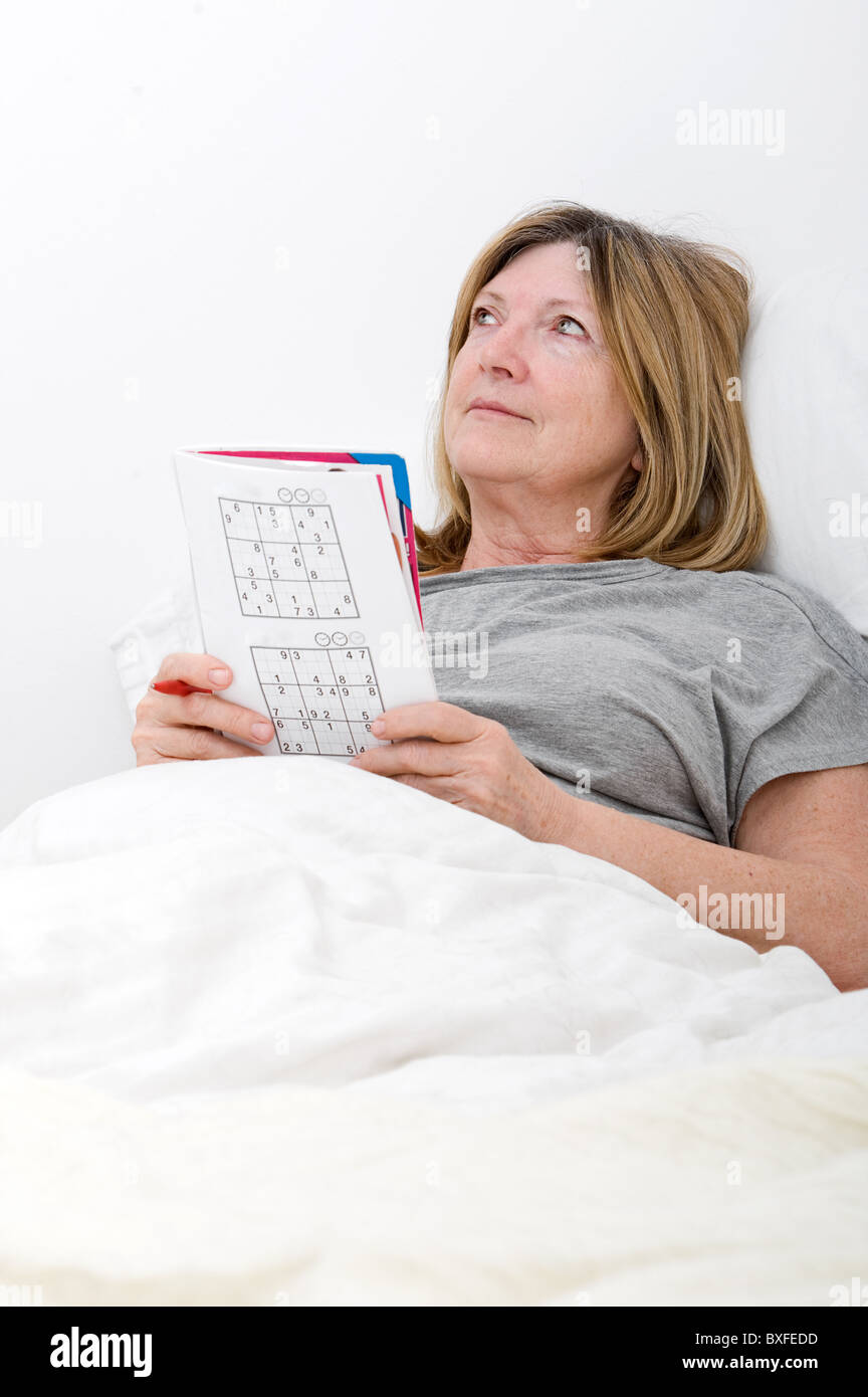Senior lady in bed playing sudoko - Stock Image