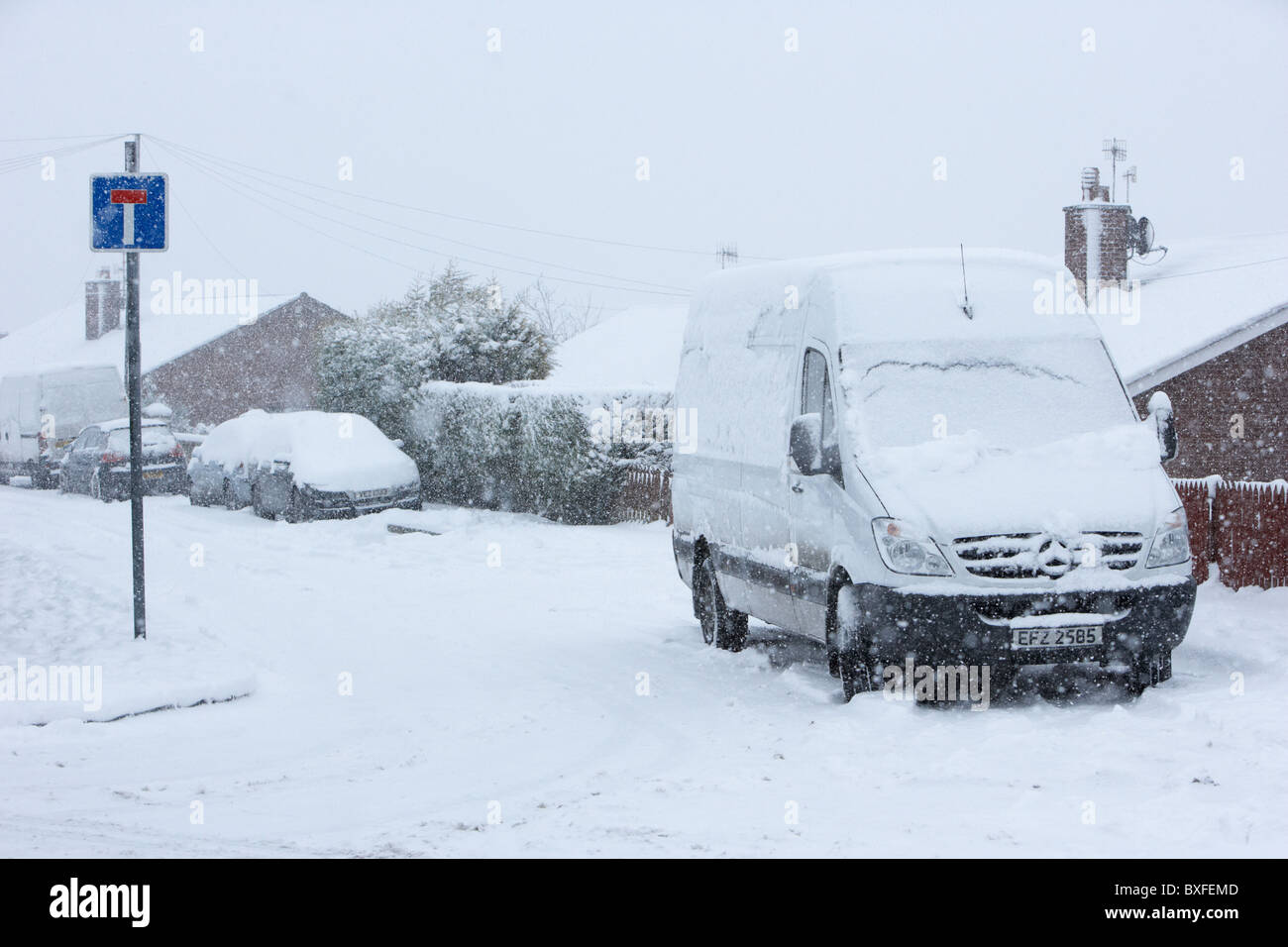 white delivery van stuck in snow on a cold snowy winters day Belfast Northern Ireland - Stock Image