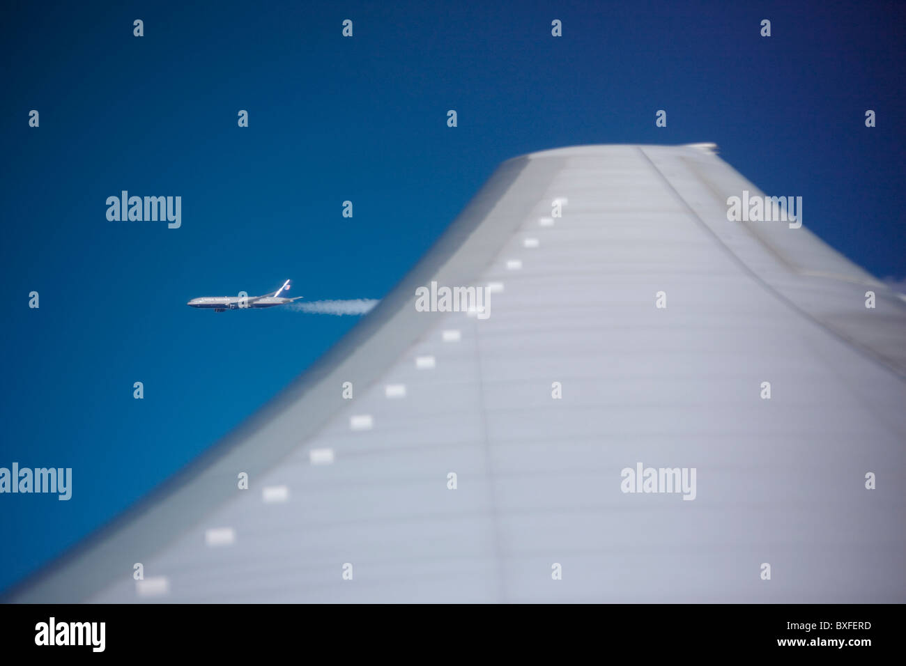 Passenger jet aircraft viewed across plane wing from porthole of another in flight on route to America - Stock Image