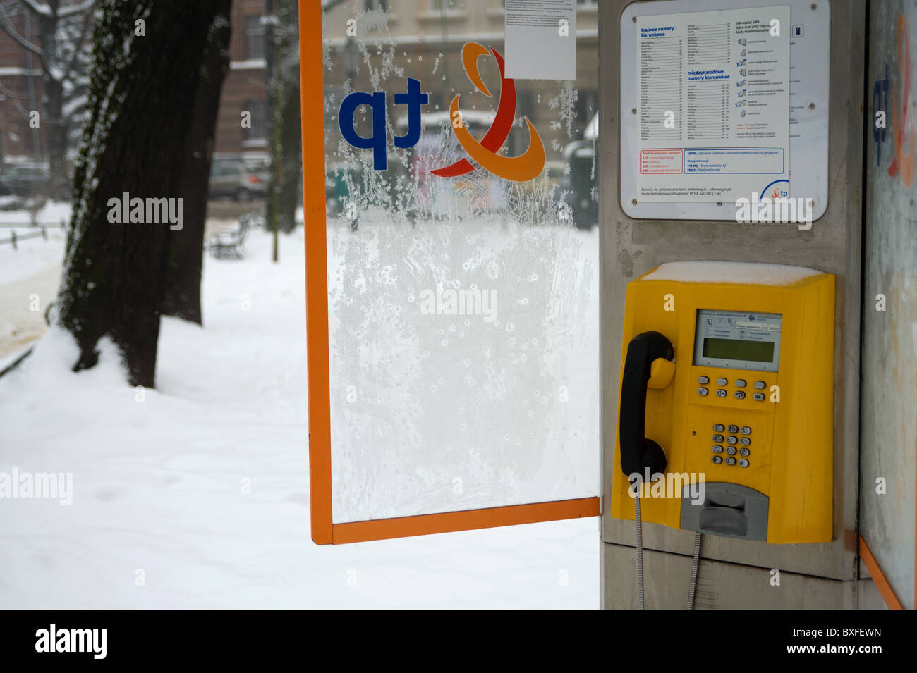 A bright colored yellow pay telephone kiosk seen contrasted against recent snow-fall in the Planty area of Krakow. - Stock Image