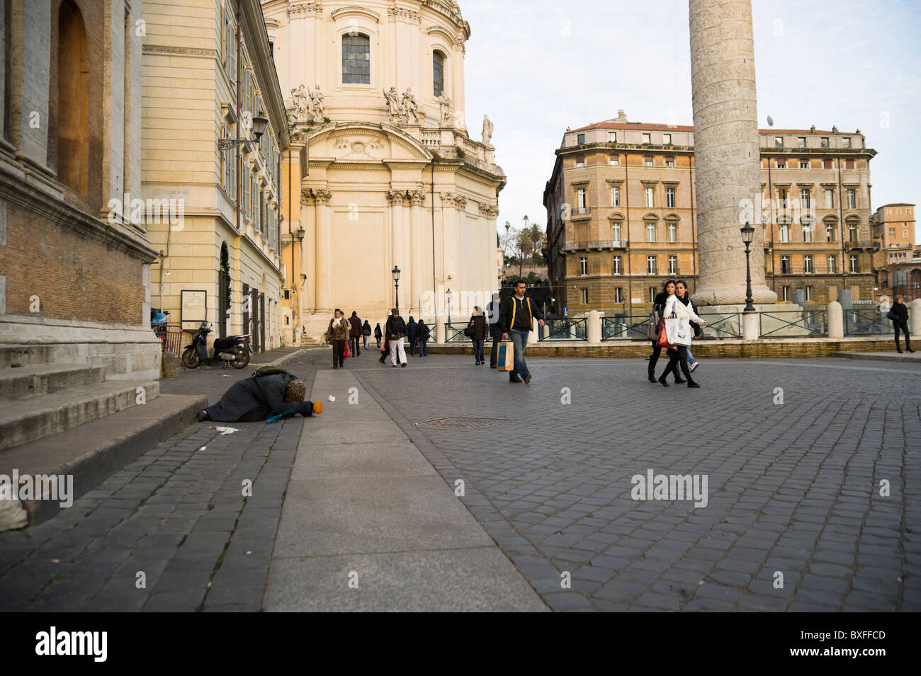Rome, beggar by Trajan's Column with passerbies - Stock Image