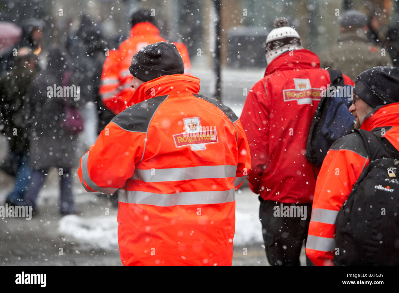 royal mail postmen out walking on a cold snowy winters day Belfast Northern Ireland - Stock Image