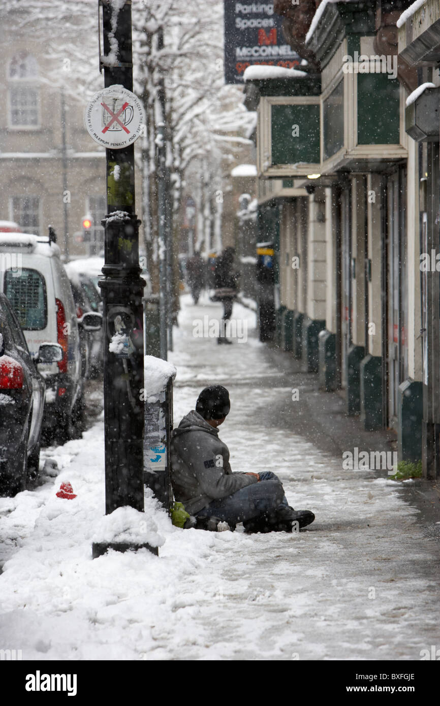 street beggar sitting in the snow on a cold snowy winters day Belfast Northern Ireland - Stock Image