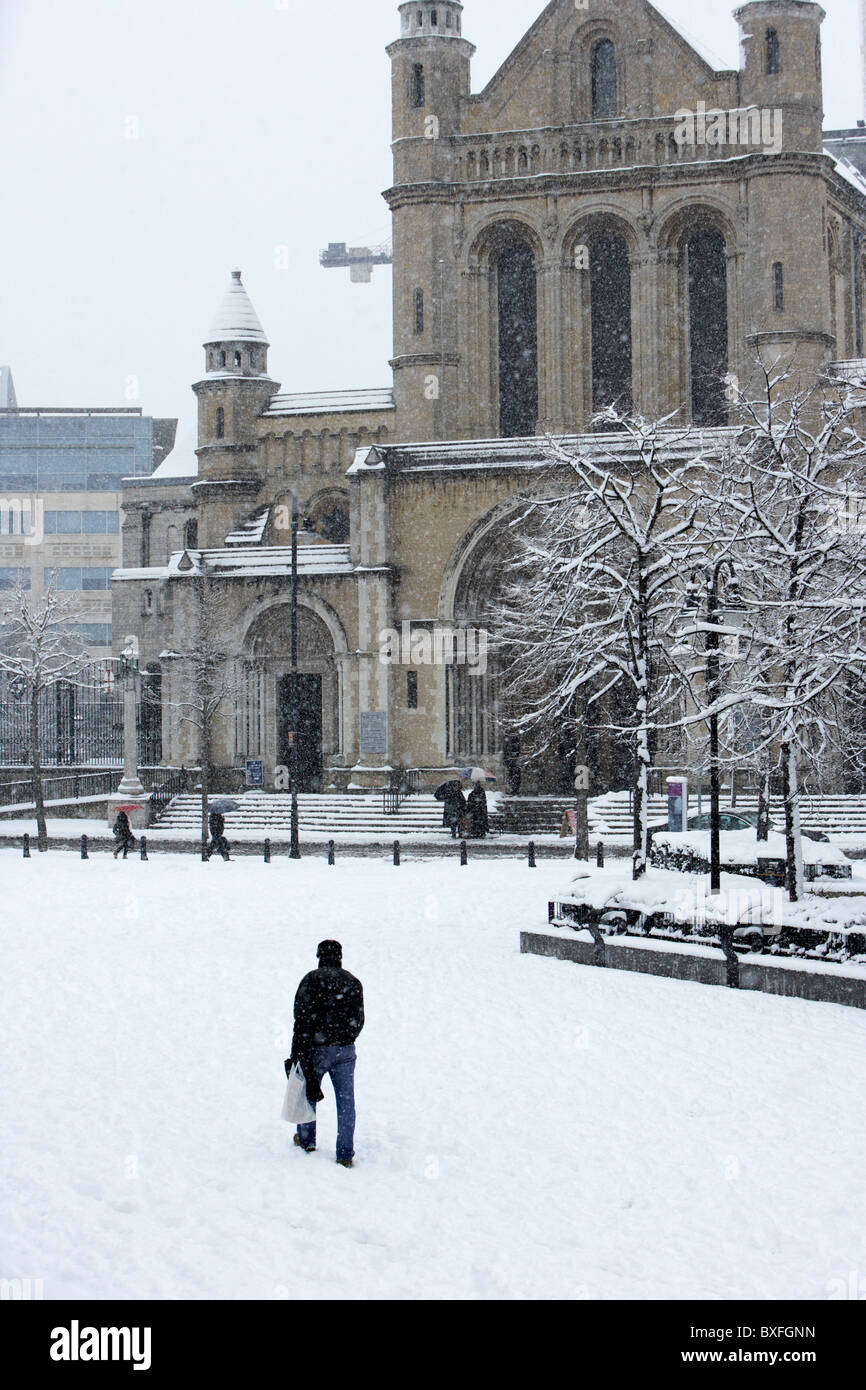 man walking through writers square outside st annes cathedral on a cold snowy winters day Belfast Northern Ireland - Stock Image