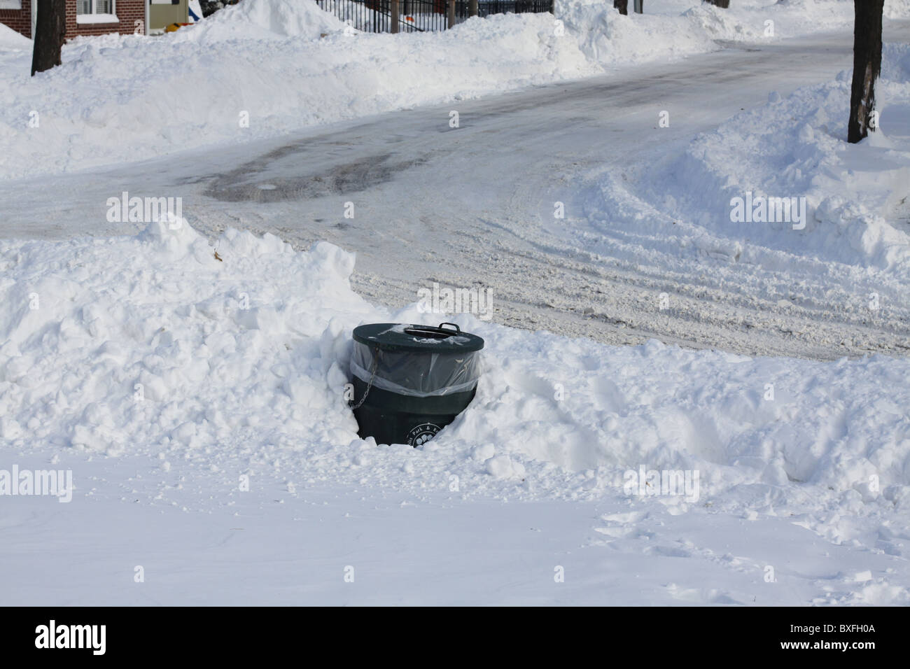 A trash can buried in snow on a street corner in Minneapolis, Minnesota. - Stock Image