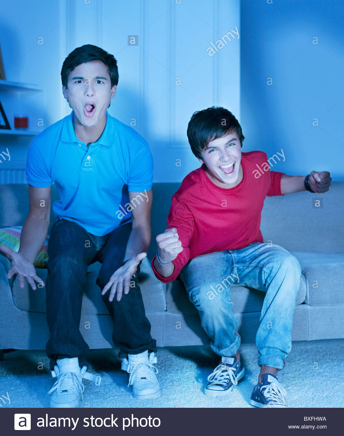Shouting teenage boys watching television - Stock Image