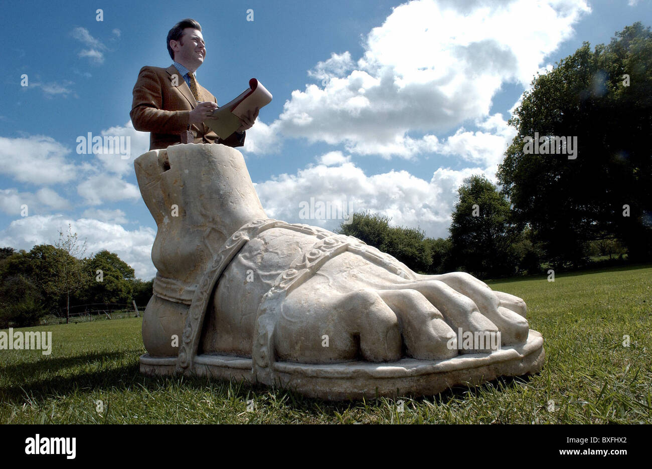 A Sotheby's auctioneer with a gigantic marble foot from a Roman statue at a sale of garden statuary Stock Photo