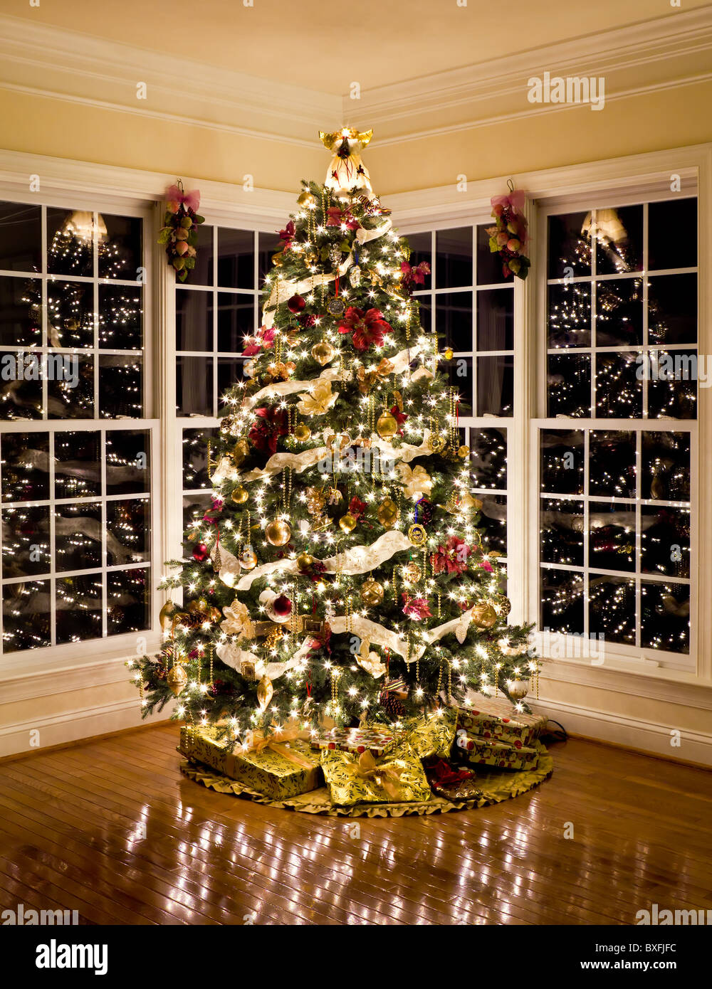 Christmas tree with presents and lights reflecting in windows around the tree in a home living room - Stock Image