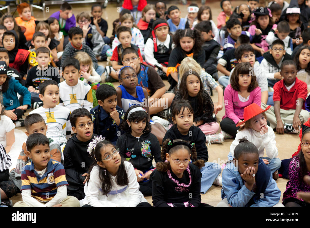 Elementary 3rd grade students listen to children's author Derrick Barnes read from one of his books at school - Stock Image