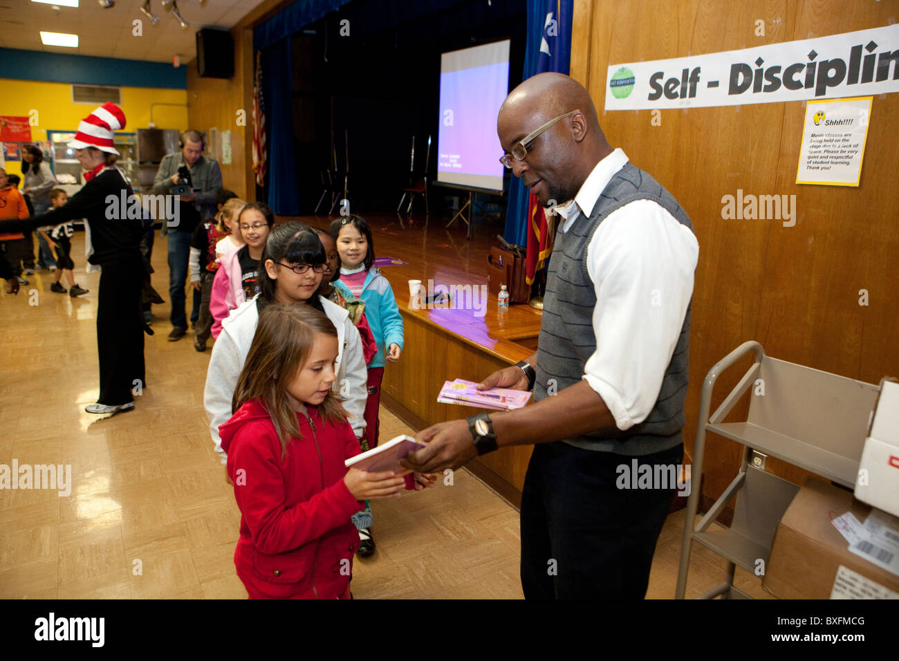 Third graders line up to receive free copy of children's author Derrick Barnes' book at school assembly - Stock Image
