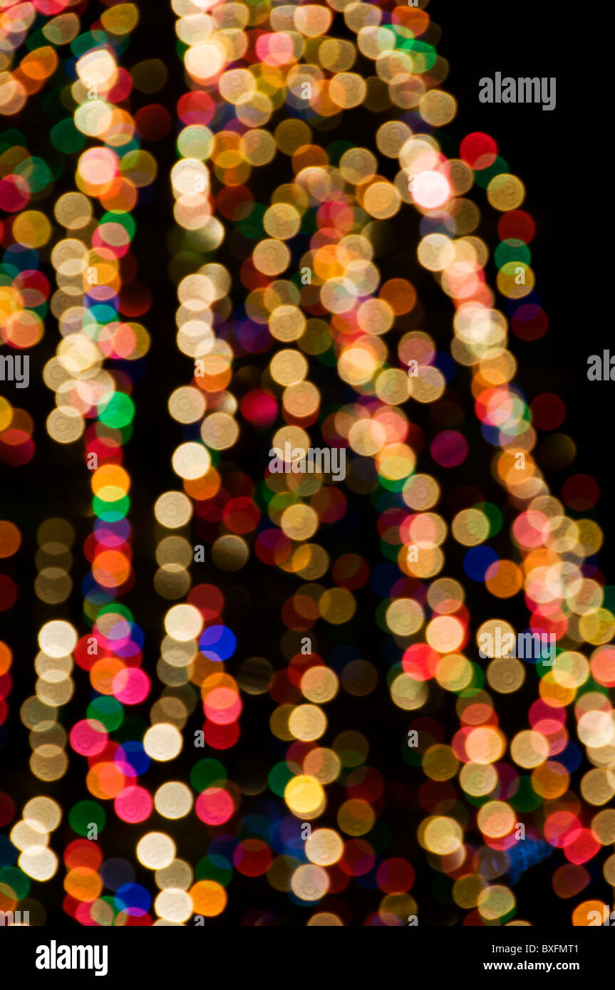 Out of focus lights glow on an outdoor Christmas tree. - Stock Image