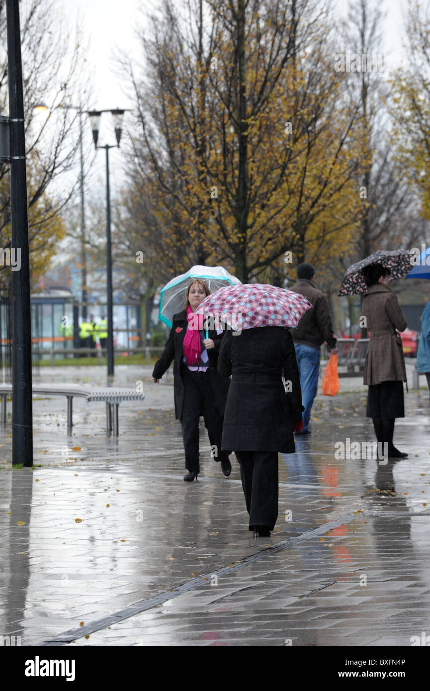 Women office workers walking in the rain on a wet pavement with umbrellas up on a cold grey November day in Oldbury - Stock Image