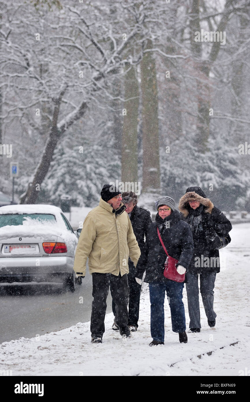 Pedestrians walking on slippery road in winter in the snow, Belgium - Stock Image