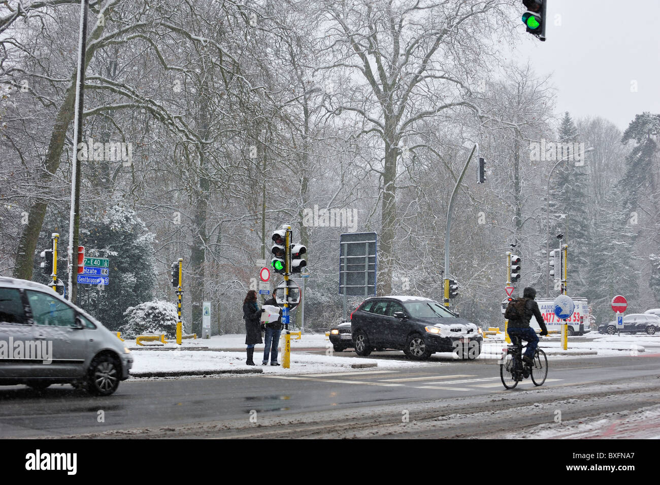 Cars and cyclist driving on slippery road in winter in the snow, Ghent Belgium - Stock Image