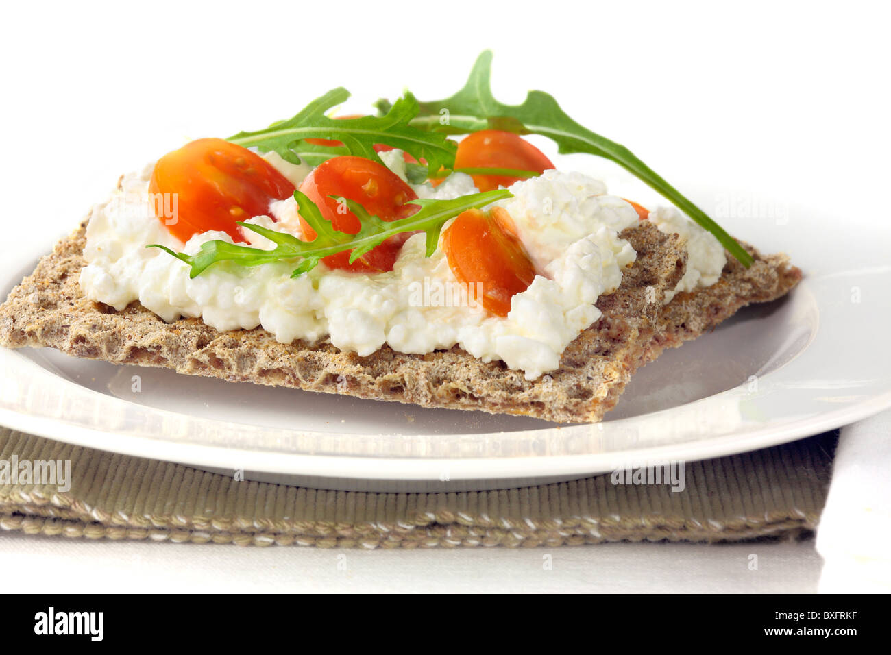 Ryvita with cottage cheese and tomato and rucola - Stock Image