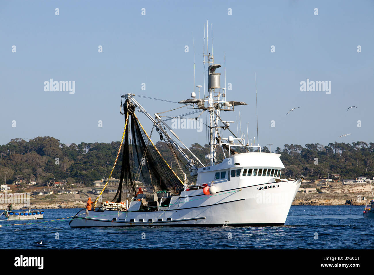 A fishing boat heads out of Monterey harbor - California. - Stock Image