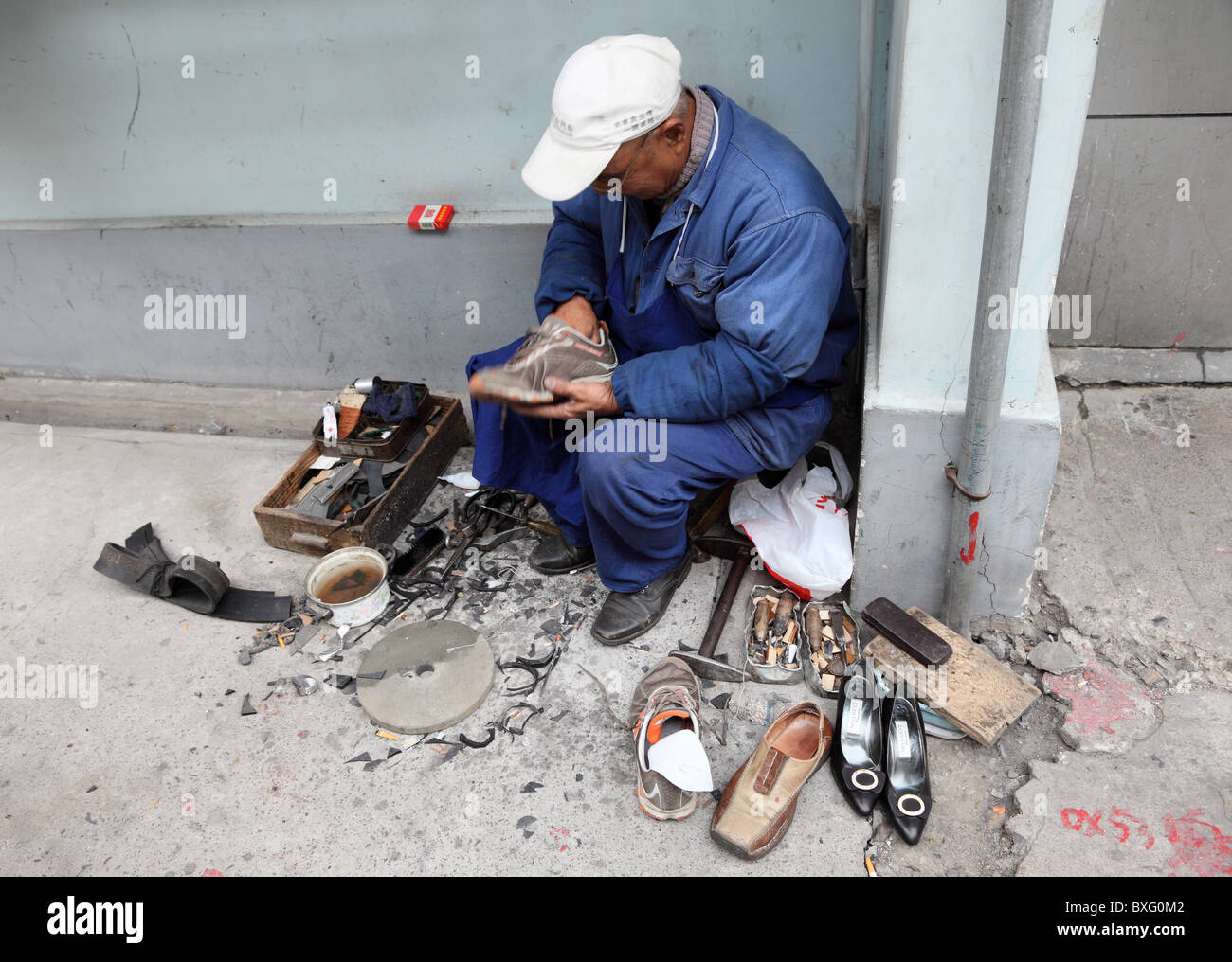 Chinese shoemaker at work in Shanghai. Photo taken at  23rd of November 2010 Stock Photo
