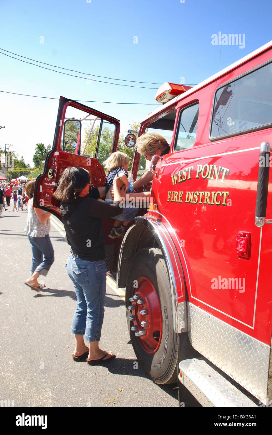 Mother lifts her little boy into a fire truck Stock Photo