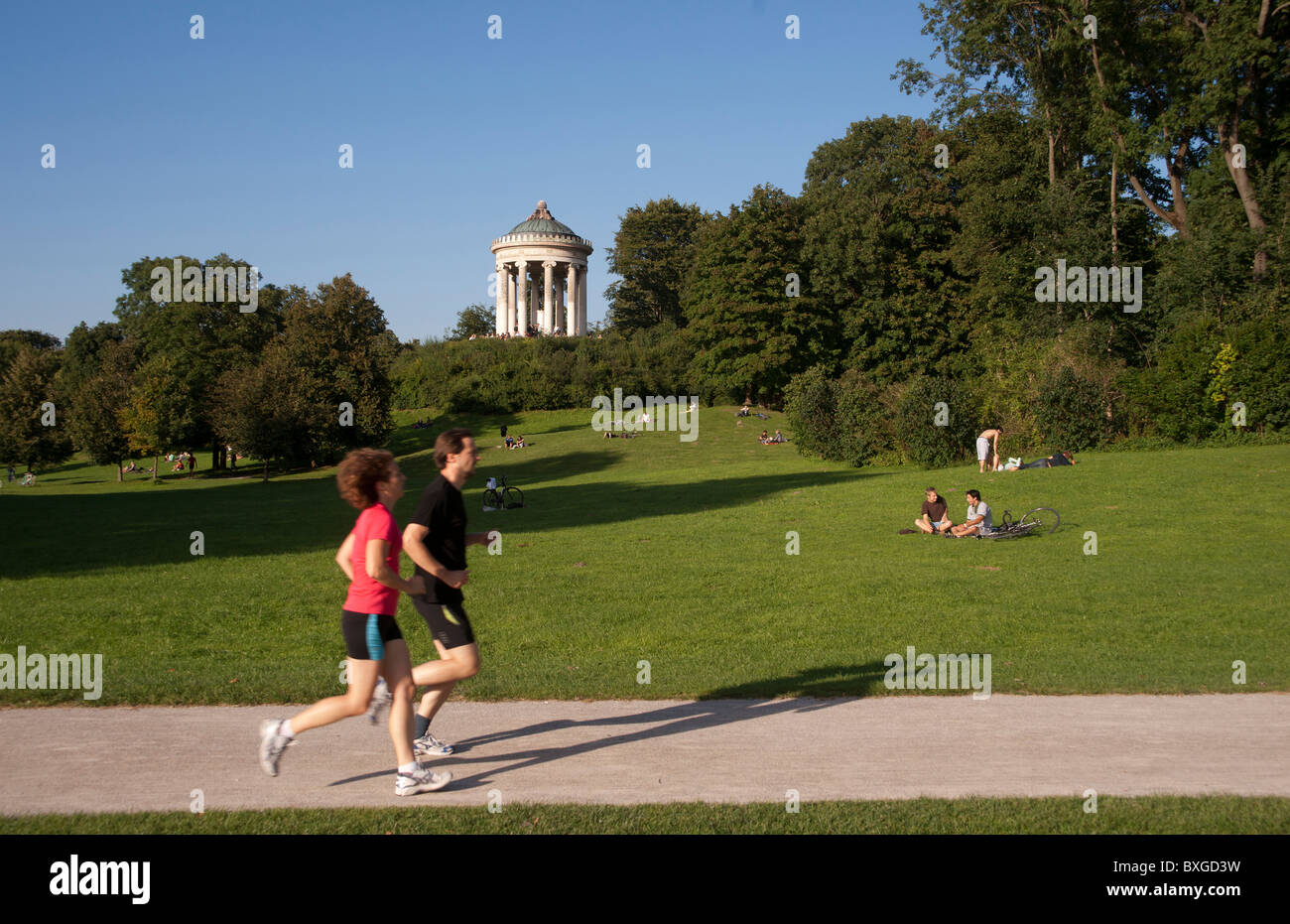 Runners in the Englischer Garten Munich. Monopteros in the background. - Stock Image
