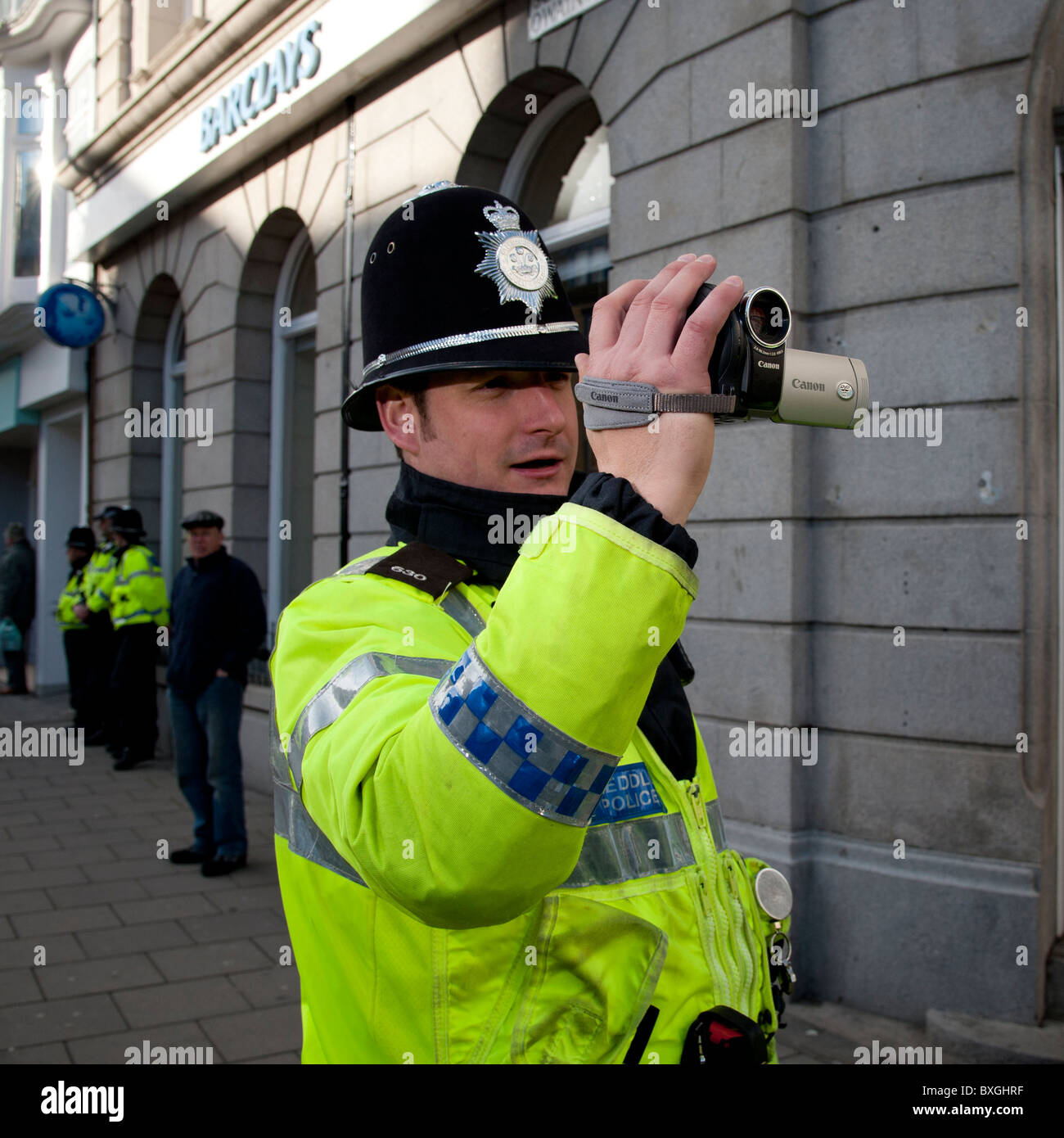 Police FIT forward intelligent team officer videoing student protest against education cuts, Aberystwyth Wales UK - Stock Image