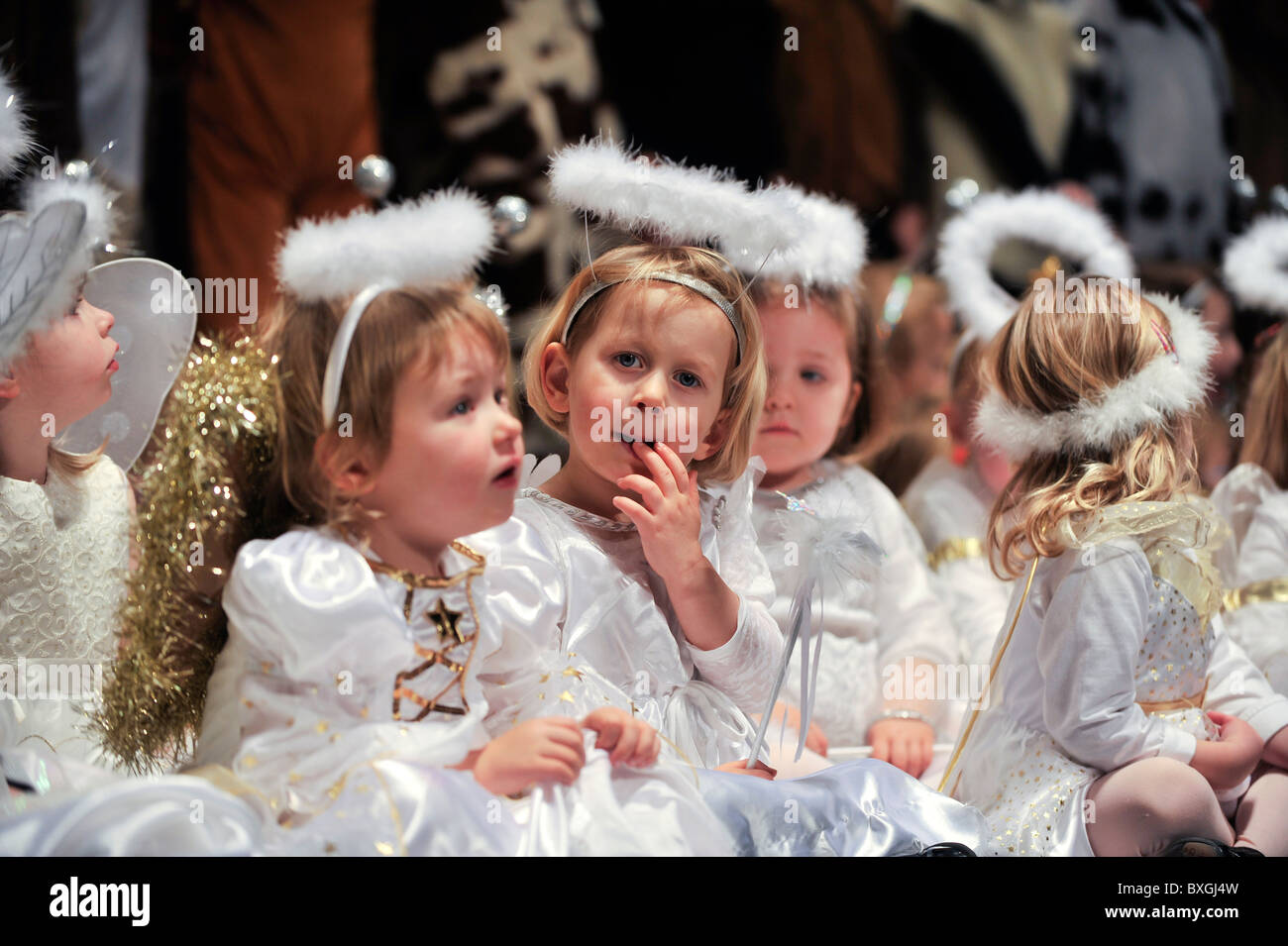 Children dressed as angels performing in a primary school christmas nativity play, UK - Stock Image