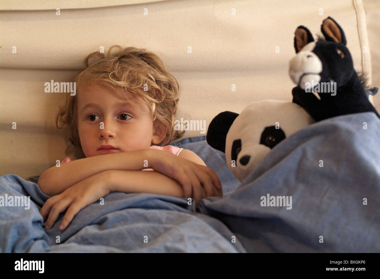 Little girl in bed watching TV surrounded by her favourite toys. - Stock Image