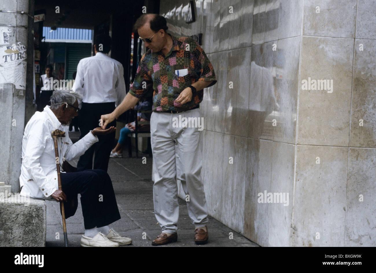Costa Rica, San Jose, Mann gibt alten Bettler mit Kruecke Geld man giving old beggar with crutches money - Stock Image