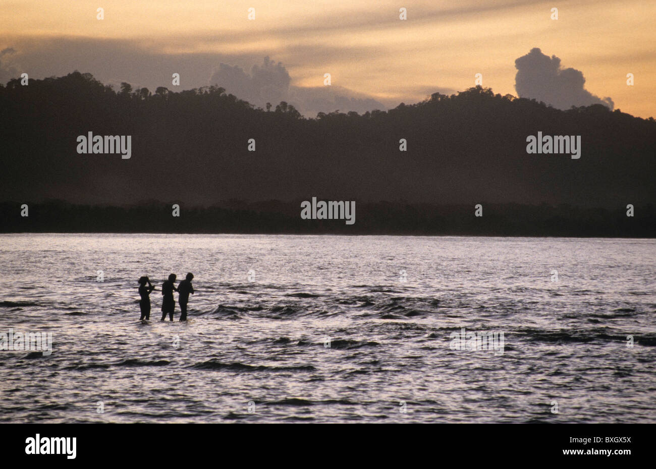 Costa Rica, puerto viejo, three people two men one woman fishing at sunset - Stock Image