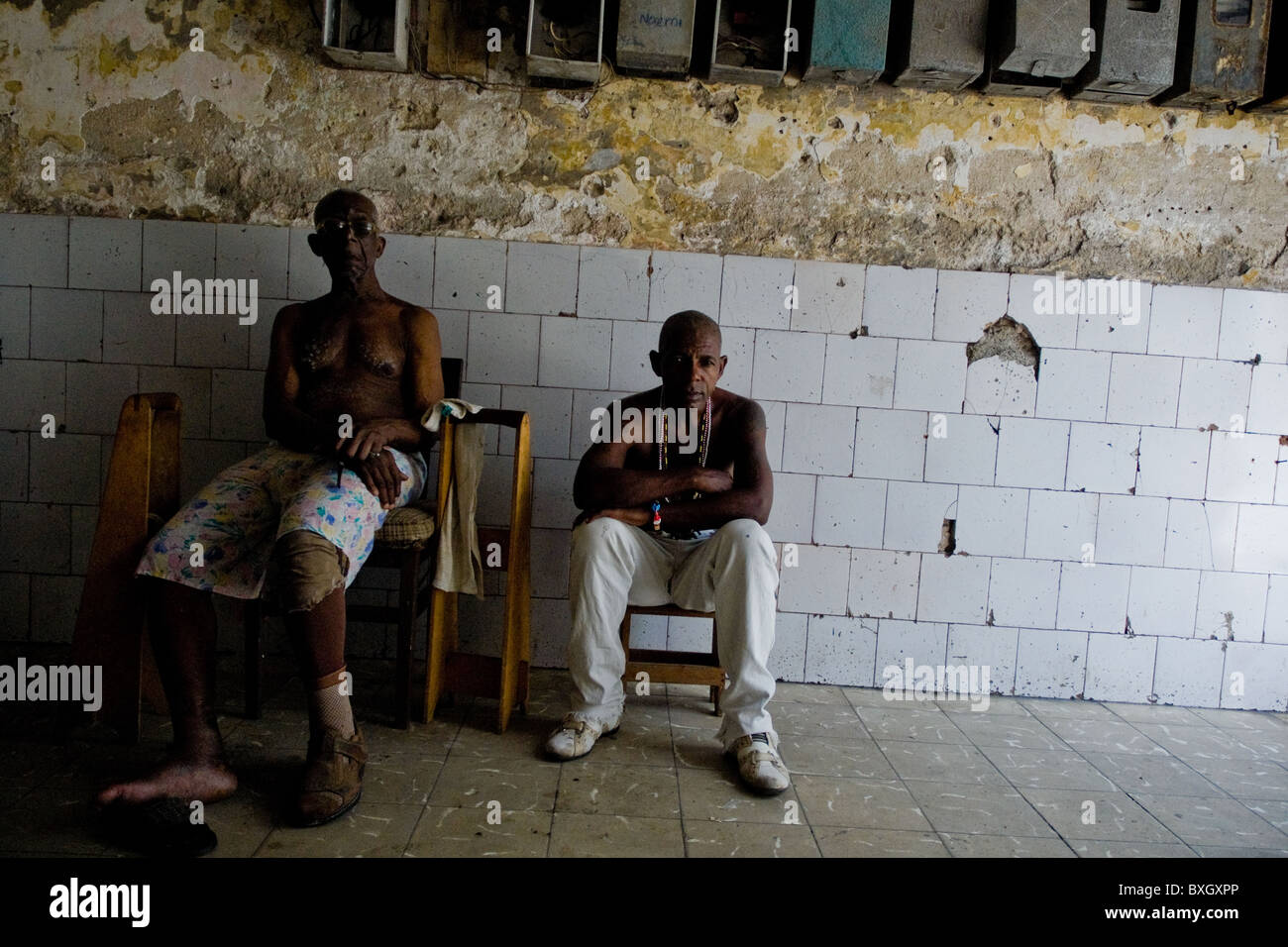 Cuban men, the Afro-Cuban religion belivers, sitting in a passage of the old house in Havana, Cuba. Stock Photo