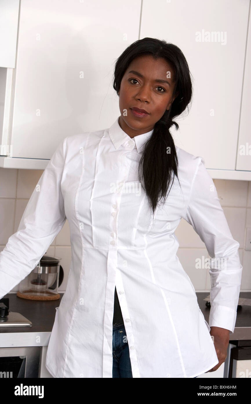 Afro Caribbean woman with long straightened hair in white shirt and jeans in kitchen - Stock Image