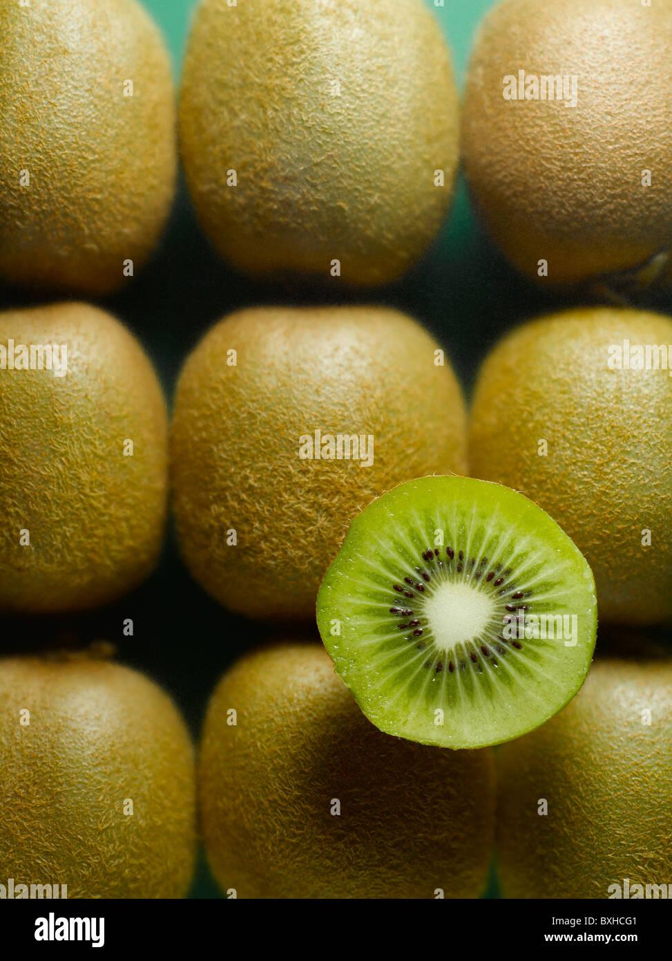 whole kiwi fruit with sliced half kiwi on green background - Stock Image