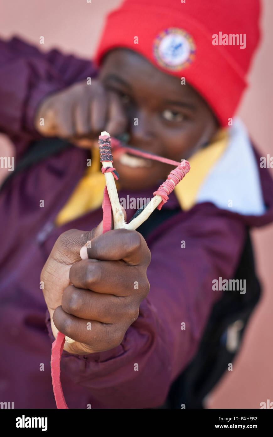 Boy aiming to the camera with his sling, Lüderitz, Namibia, Africa - Stock Image