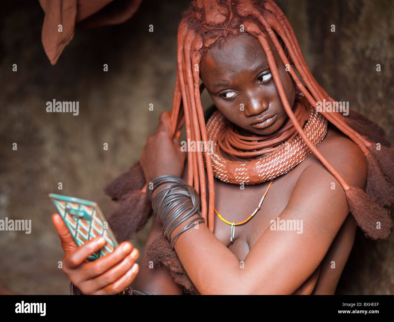 Himba woman in her hut styling her hairdo in a village near Epupa Falls, Namibia, Africa. Stock Photo