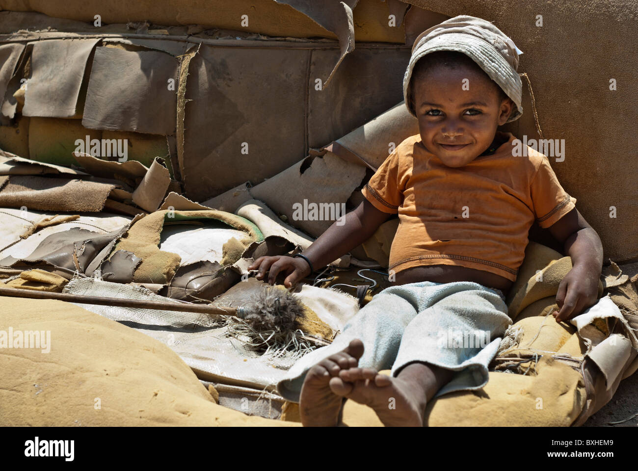 Girl on a destroyed couch, Opuwo, Namibia, Africa - Stock Image