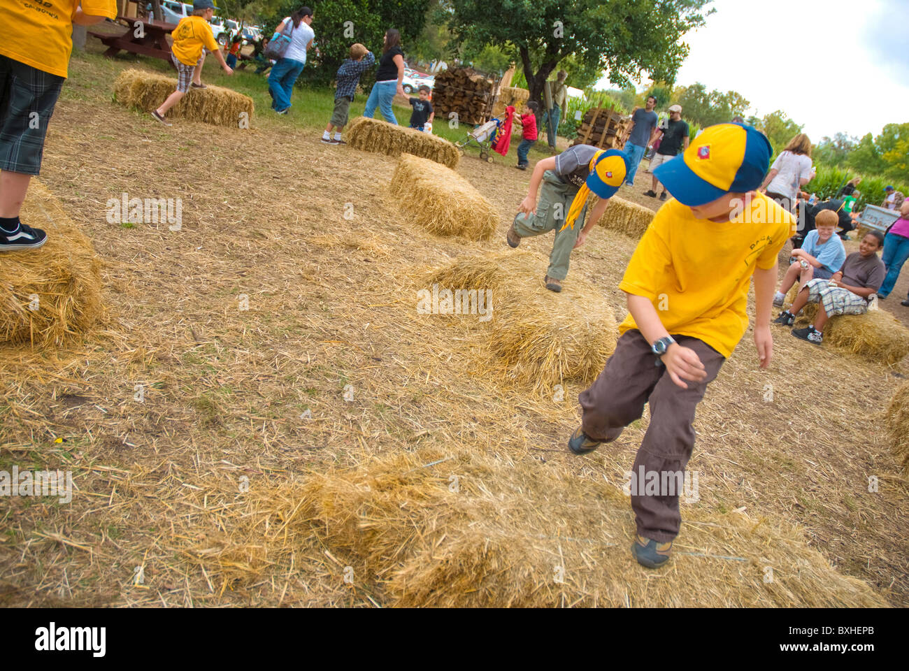 Cub Scouts jumping on bales of hay on a farm Stock Photo